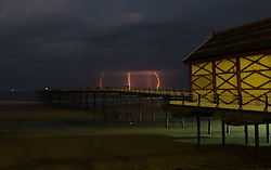 © Licensed to London News Pictures.02/07/15<br /> Saltburn by the Sea, UK. <br /> <br /> Lightning strikes can be seen beyond the pier off the north sea coast after what has been one of the hottest days of the year with heavy thunderstorms affecting many parts of the country.<br /> <br /> Photo credit : Ian Forsyth/LNP