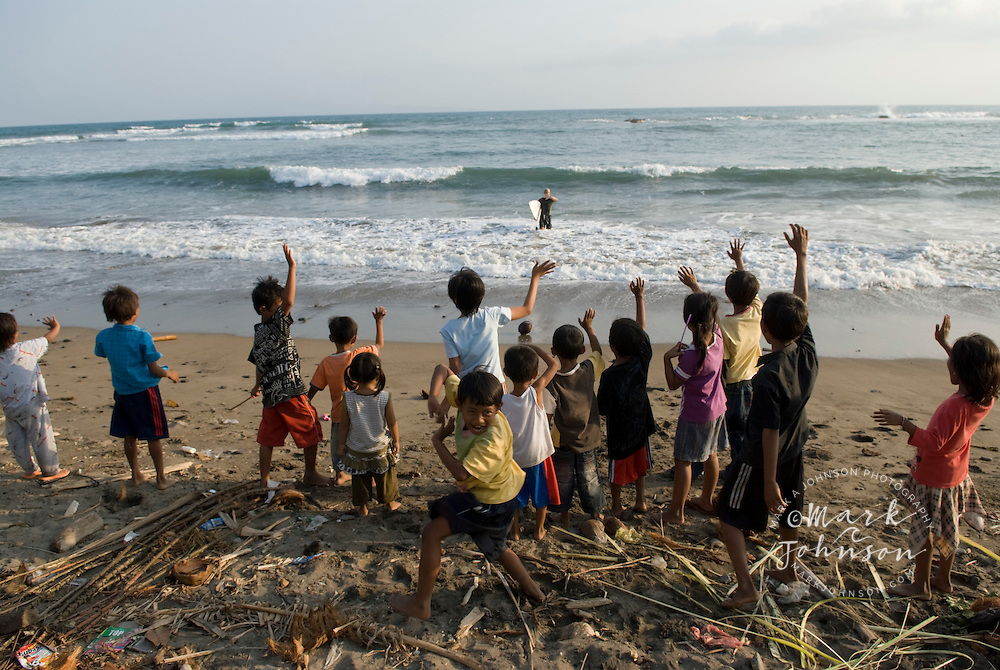 Children welcoming surfer back to shore, S. Sumatra, Indonesia