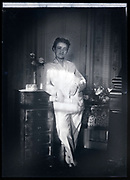 woman standing in pajamas with strong morning sunlight circa 1930s