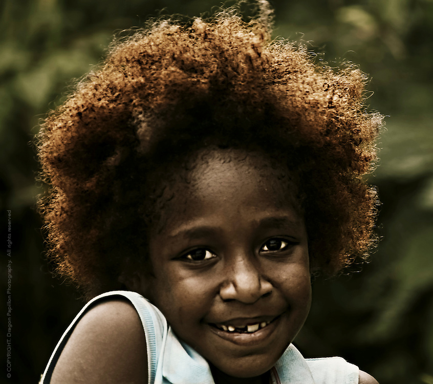 portrait of young local South Pacific Islander girl from Vanuatu with large smile and front tooth missing