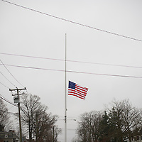 Centered between 2 churches on Main Street in Newtown, CT, the American flag flies at half mast on Sunday, December 16, 2012, 2 days following a mass shooting of 20 children and 7 adults at Sandy Hook Elementary School.
