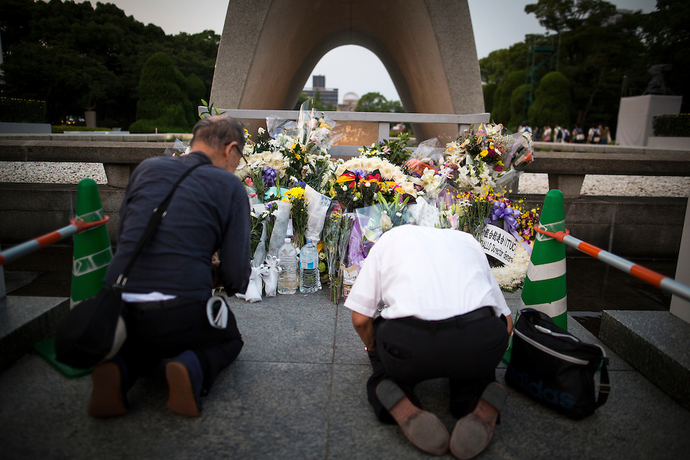 """HIROSHIMA, JAPAN - AUGUST 5 : Visitors lays flowers and pray for the atomic bomb victims in front of the cenotaph ahead of the 71st anniversary of the atomic bombing on Hiroshima at Hiroshima Peace Memorial Park in Hiroshima, western Japan, Friday afternoon, August 5, 2016. Japan marked the 71st anniversary of the atomic bombing on Hiroshima. On August 6, 1945, during World War II, the United States dropped a uranium gun-type atomic bomb named """"Little Boy"""" on the city of Hiroshima which instantly killed an estimated 80,000 people, tens of thousands more would later die of radiation exposure. Three days later, a second American B-29 bomber dropped a plutonium implosion-type bomb """"Fat Man"""" on Nagasaki, killing an estimated 40,000 people.  (Photo: Richard Atrero de Guzman/NURPhoto)"""