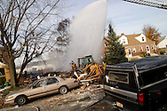 Firefighters pour water on what's left of a house near what appears to be a gas-line explosion on Wayne Drive in Fairborn, Saturday, November 12, 2011.  The house behind the backhoe was destroyed, and the house to its left has major structural damage.