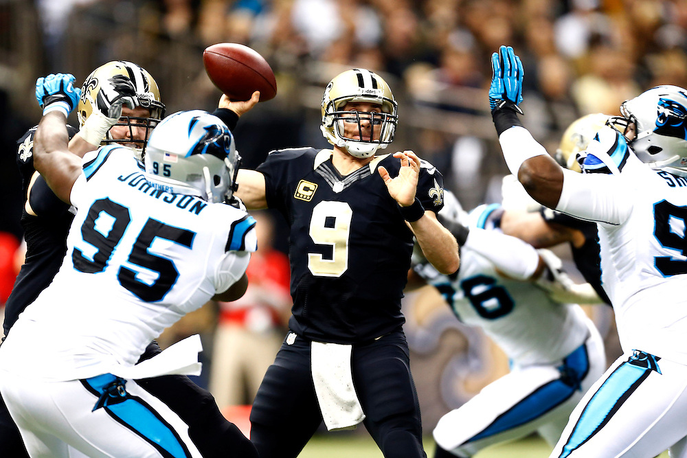 NEW ORLEANS, LA - DECEMBER 8:  Drew Brees #9 of the New Orleans Saints throws a pass under pressure from the Carolina Panthers at Mercedes-Benz Superdome on December 8, 2013 in New Orleans, Louisiana.  (Photo by Wesley Hitt/Getty Images) *** Local Caption *** Drew Brees