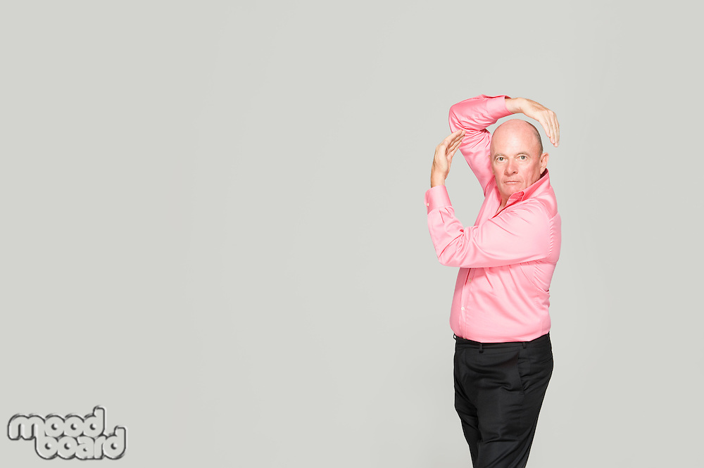 Elderly man in a pink shirt strikes a pose