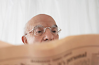 Senior man in spectacles reading newspaper close up