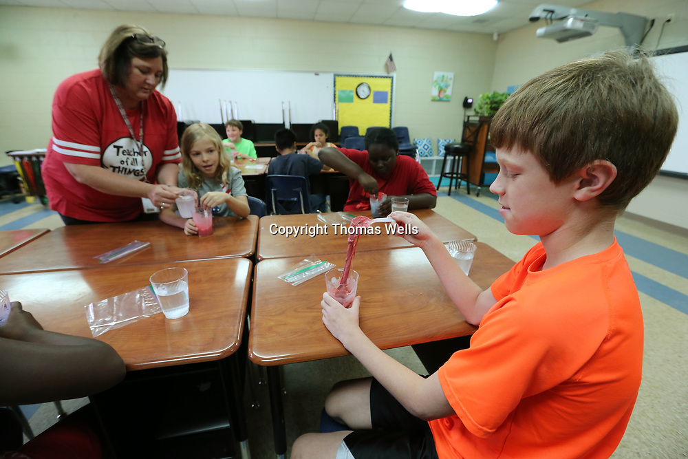 Blake Evans uses a spoon to play wit his slime as part of an experiment during his last day of school at Corinth Elementary School on Thursday.