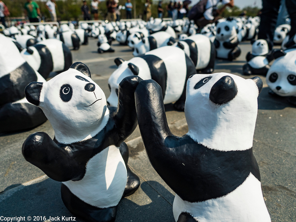 "04 MARCH 2016 - BANGKOK, THAILAND: Some of the 1600 paper maché pandas in the ""1600 Pandas+ World Tour in Thailand: For the World We Live In and the Ones We Love"" exhibit on Sanam Luang in Bangkok. The 1600 paper maché pandas, an art installation by French artist Paulo Grangeon will travel across Bangkok and parts of central Thailand for the next week and then will be displayed at Central Embassy, a Bangkok shopping mall, until April 10. The display of pandas in Thailand is benefitting World Wide Fund for Nature - Thailand and is sponsored by Central Embassy with assistance from the Tourism Authority of Thailand and Bangkok Metropolitan Administration and curated by AllRightsReserved Ltd.     PHOTO BY JACK KURTZ"