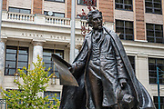 2017 statue of William H. Seward (1801-1872) in Juneau, Alaska, USA. As US Secretary of State, William H. Seward oversaw the Alaska purchase, transferred from the Russian Empire in 1867. The City and Borough of Juneau is the capital city of Alaska and the second largest city in the USA by area (only Sitka is larger). This unified municipality lies on Gastineau Channel in the Alaskan panhandle. Juneau has been the capital of Alaska since 1906, when the government of what was the District of Alaska was moved from Sitka. The city is named after a gold prospector from Quebec, Joe Juneau. Isolated by rugged terrain on Alaska's mainland, Juneau can only be reached by plane or boat. Downtown Juneau sits at sea level under steep mountains up to 4000 feet high, topped by Juneau Icefield and 30 glaciers.
