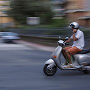 Blurred motion image of man riding Piaggio Vespa ET4 scooter, Levanto, Italy<br />