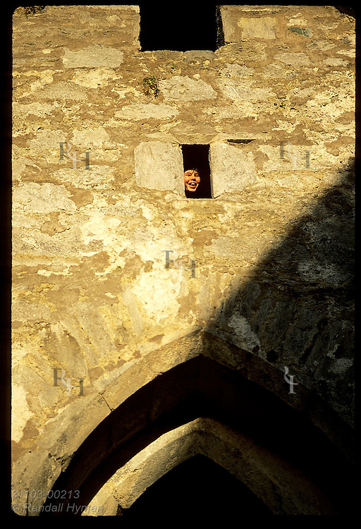 Girl peers from window opening on upper floor of Muckross Abbey, built by Franciscan friars in 1400s; Killarney Natl Park, Ireland.