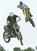 Jason Thorne (L) and Kenny Yoho fly over a jump at a bar in Samsula, Florida during Bike Week in Daytona Beach, Florida March 9, 2005. The annual ten-day event attracts motorcyclists of all varieties with over 500,000 expected this year.  REUTERS/Rick Wilking