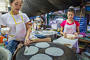 "03 OCTOBER 2012 - BANGKOK, THAILAND:  Women make roti, a very light and delicate type of flat bread in Khlong Toey Market in Bangkok. Khlong Toey (also called Khlong Toei) Market is one of the largest ""wet markets"" in Thailand. Thousands of people shop in the sprawling market for fresh fruits and vegetables as well meat, fish and poultry every day.      PHOTO BY JACK KURTZ"