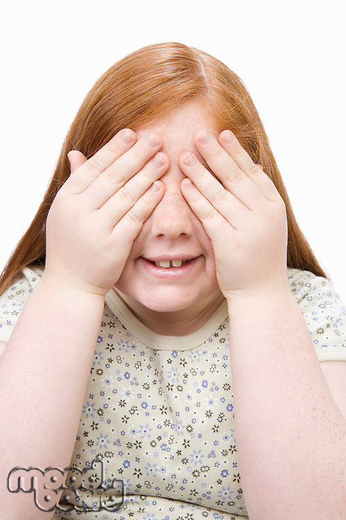 Portrait of teenage girl covering eyes with hands