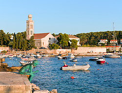 Around the corner from Hvar's busy watarfront and promenade lies a picturesque small boat harbor and an in-town swimming area.  Late day light.