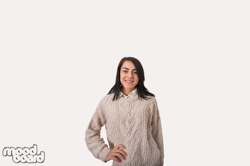 Portrait of confident businesswoman with hand on hip standing against gray background