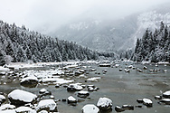 Snow falling on the Chilkoot River in Southeast Alaska. Winter. Afternoon.