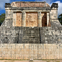 North Temple of Great Ballcourt at Chichen Itza, Mexico<br /> At either end of the I-shaped Great Ballcourt are temples. The southern one is in ruins. The Northern Temple typically represented the heavens. This is also referred to as the Temple of the Bearded Man because of a relief inside showing a figure with facial hair, a rarity among Mesoamerican archeological sites. The purpose of this three-tiered masonry building is uncertain. Some experts believe it was the ruler's viewing platform during important ceremonies. From this position, the acoustics from the ballcourt are so excellent you can hear someone speak at the far end of the alley.