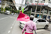 "24 AUGUST 2013 - BANGKOK, THAILAND:     A tout waves a flag advertising a new real estate development while a BMW passes a Toyota showroom on Sukhumvit Road in Bangkok. Free spending Thais were shocked when Thailand entered a ""technical"" recession this month after the economy shrank by 0.3% in the second quarter of the year. The 0.3% contraction in gross domestic product between April and June followed a previous fall of 1.7% during the first quarter of 2013. The contraction is being blamed on a drop in demand for exports, a drop in domestic demand and a loss of consumer confidence. At the same time, the value of the Thai Baht against the US Dollar has dropped significantly, from a high of about 28Baht to $1 in April to 32THB to 1USD in August.  PHOTO BY JACK KURTZ"