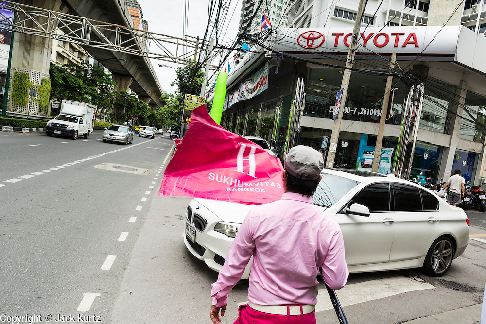 """24 AUGUST 2013 - BANGKOK, THAILAND:     A tout waves a flag advertising a new real estate development while a BMW passes a Toyota showroom on Sukhumvit Road in Bangkok. Free spending Thais were shocked when Thailand entered a """"technical"""" recession this month after the economy shrank by 0.3% in the second quarter of the year. The 0.3% contraction in gross domestic product between April and June followed a previous fall of 1.7% during the first quarter of 2013. The contraction is being blamed on a drop in demand for exports, a drop in domestic demand and a loss of consumer confidence. At the same time, the value of the Thai Baht against the US Dollar has dropped significantly, from a high of about 28Baht to $1 in April to 32THB to 1USD in August.  PHOTO BY JACK KURTZ"""