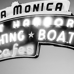 "Santa Monica panorama of the Santa Monica Pier sign in black and white.  Panorama picture ratio is 1:3. The famous Santa Monica Pier sign says ""Santa Monica Yacht Harbor Sport Fishing Boating Cafes"". Santa Monica Pier is a landmark located in Los Angeles County Southern California."
