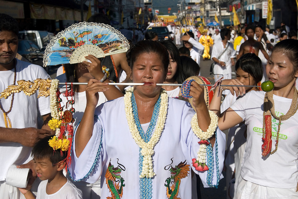 Female mediums in the Phuket Vegetarian Festival Street Procession, Phuket Town, Thailand.....** The Phuket Vegetarian Festival celebrates the beginning of Taoist Lent, when devout Chinese abstain from eating all meat and other vices.  The festival takes place on the first 9 days of the 9th lunar month of the Chinese calendar.  Everyone dresses in white and shopkeepers set up small alters with offerings of incense, flowers, candles, fruit, and 9 cups of tea to the 9 emperor deities honored by the festival. ....Mediums bring the 9 gods to earth entering a trance state and piercing themselves with all kinds of objects, climbing knife ladders, and walking on hot coals.  The mediums participate in daily processions through town where they stop at the store front alters, drink one of the 9 cups of tea, and offer blessings to the merchants.  The shopkeepers stand in prayer like fashion respecting the mediums that are temporarily possessed by the deity.  The self torture is done to shift evil from individuals to the mediums and bring the community good luck.....Young men carry alters of the deity images though town which culminates at central locations where merchants cover them with huge strands of firecrackers and larger explosives.  The louder and longer blasts are best to drive away evil spirits.  The experience is deafening and engulfs the men and alters in a painful barrage of fire and smoke.  ....Chinese tour groups come to witness since there is no record of this type celebration of Taoist Lent in China.  The festival is believed to have started when a Chinese theatre troupe fell ill for failing to honor the 9 emperor gods of Taoism.  They were quickly cured when they adhered to the 9 day ritual now held each year promoting inner peace, brightness, and proper hygiene.  ..