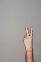 Man holding up two fingers against grey background
