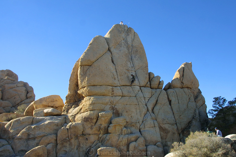 Adam belays for Doug D'Aluisio climbing a boulder at Joshua Tree National Monument, California. Christmas road trip from Napa, California to Sedona, Arizona and back. MODEL RELEASED.
