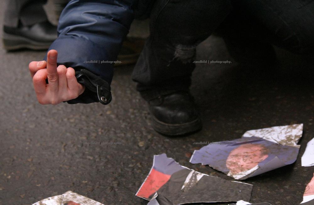 Ein Demonstrant streckt seinen Mittelfinger in Richtung eines zerrissenen Putin-Portraits. Nachdem rund 2000 Menschen in Moskau eine Kundgebung gegen den russischen Praesidenten Putin abhielten, durchbrachen hunderte Oppositionelle Polizeisperren, um zur Zentralen Wahlkommision vorzudringen. Kraefte der Sondereinheit OMON stoppte den Protest und verhaftete mehrere Demonstranten. Auch der ehemalige Schachweltmeister und populaere Oppositionelle Garry Kasparow wurde inhaftiert. A protester shows his middel finger to a dropped down Portrait of Putin. After an opposition gathering in Moscow several thousand protesters tried to march on the Central Election Commission. After they broke police lines russian police broke up the march and detained serveral protesters, also the protest leader, former chess champion Garry Kasparov.