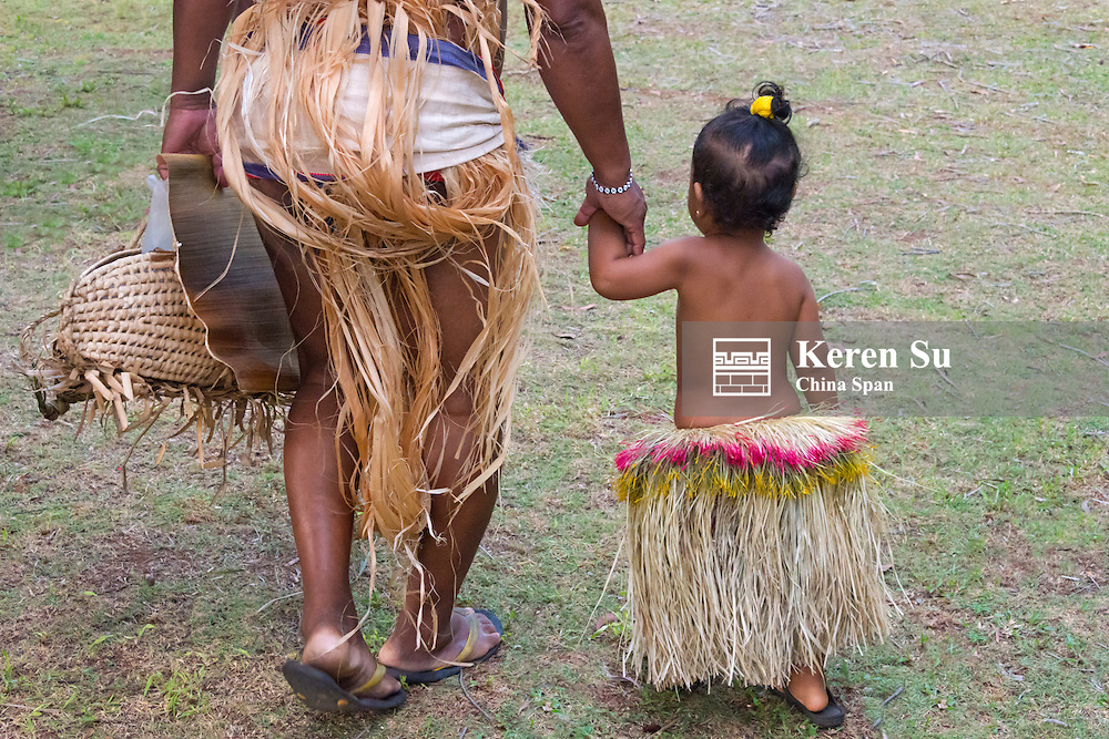 Yapese man with little girl in grass skirt at Yap Day Festival, Yap Island, Federated States of Micronesia