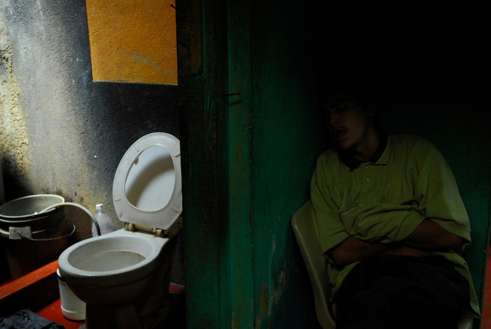 "Herson Rodriguez falls asleep outside the bathroom at Casa Hogar, a rehabilitation home for alcohol and drug addicts, outside of Antigua, Guatemala. Rodriguez has been living at Casa Hogar for 2 weeks and hopes to kick his addiction to alcohol...Casa Hogar currently houses 44 men (with a maximum of 60.) Jorge Rosales, himself a former drug user, founded the home 2 years ago after he kicked his habit and left the garbage dump he had been living in for thirteen months...If accepted into Casa Hogar the voluntary residents must first spend 6 days in a first floor room of mattresses, are denied showers and must eat meals separately from other residents. Patients in the first floor zone suffer from convulsions, vomiting and other withdrawal symptoms and are monitored round the clock by a nurse. Most alcoholics who enter the program had been drinking rubbing alcohol because it is so inexpensive. ..""If they make it"" says resident Byron Rosales, ""they can join us up top."" It is up to the individual when they feel they are ready to leave the home."