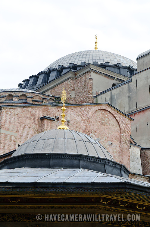 Exterior of Hagia Sophia buildings in Istanbul with multiple layers of construction and two of the building's dome's.