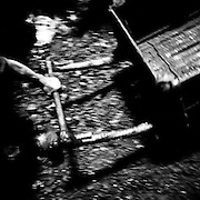 A young miner pulls an empty coal cart back into the 'rat holes'. Small sized miners are used to work in the 'rat holes' because they can fit in the tunnels which have an average diameter of 2 feet. The miners work from 7am to 1pm and from 2pm to 7pm and sometimes later. They are paid by each cart and the money is divided between themselves...In Jaintia Hills, underaged children work in unscientific, largely unmonitored and extremely dangerous underground coal mines dug out by often trafficked children using primitive methods and tools. The north eastern Indian state of Meghalaya sits on about 640 million tons of coal, with 40 million tons of that in Jaintia Hills alone which has about 5000 privately owned mines.  Photo by Suzanne Lee for Panos London