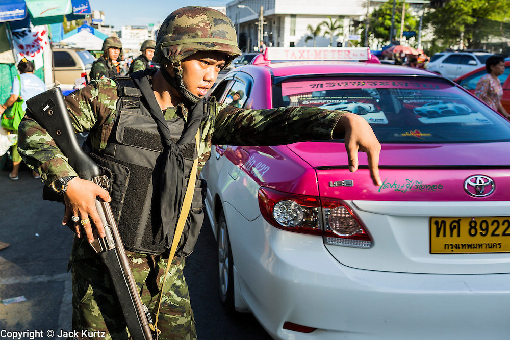 23 MAY 2014 - BANGKOK, THAILAND: A Thai soldier tries to direct traffic in Bangkok Friday morning. The Thai military seized power in a coup Thursday evening. They suspended the constitution and ended civilian rule. This is the 2nd coup in Thailand since 2006 and at least the 12th since 1932. The army has ordered both anti-government protestors in Bangkok and pro-government protestors in the suburbs to go home and arrested leaders of both groups.    PHOTO BY JACK KURTZ