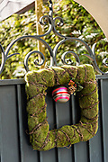 A wrought iron gate with a square Christmas wreath at a historic home on Tradd Street in Charleston, SC.