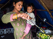 05 AUGUST 2015 - KATHMANDU, NEPAL: A woman makes lunch for her and her child in their tent in a large Internal Displaced Person (IDP) Camp in the center of Kathmandu. The camp is next to one the most expensive international hotels in Kathmandu. More than 7,100 people displaced by the Nepal earthquake in April live in 1,800 tents spread across the space of three football fields. There is no electricity in the camp. International NGOs provide water and dug latrines on the edge of the camp but the domestic waste water, from people doing laundry or dishes, runs between the tents. Most of the ground in the camp is muddy from the running water and frequent rain. Most of the camp's residents come from the mountains in northern Nepal, 8 - 12 hours from Kathmandu. The residents don't get rations or food assistance so every day many of them walk the streets of Kathmandu looking for day work.    PHOTO BY JACK KURTZ