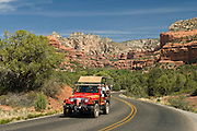 Red Rock Jeep Tours on road in Boynton Canyon, with the Enchantments in the distance; Sedona, Arizona.