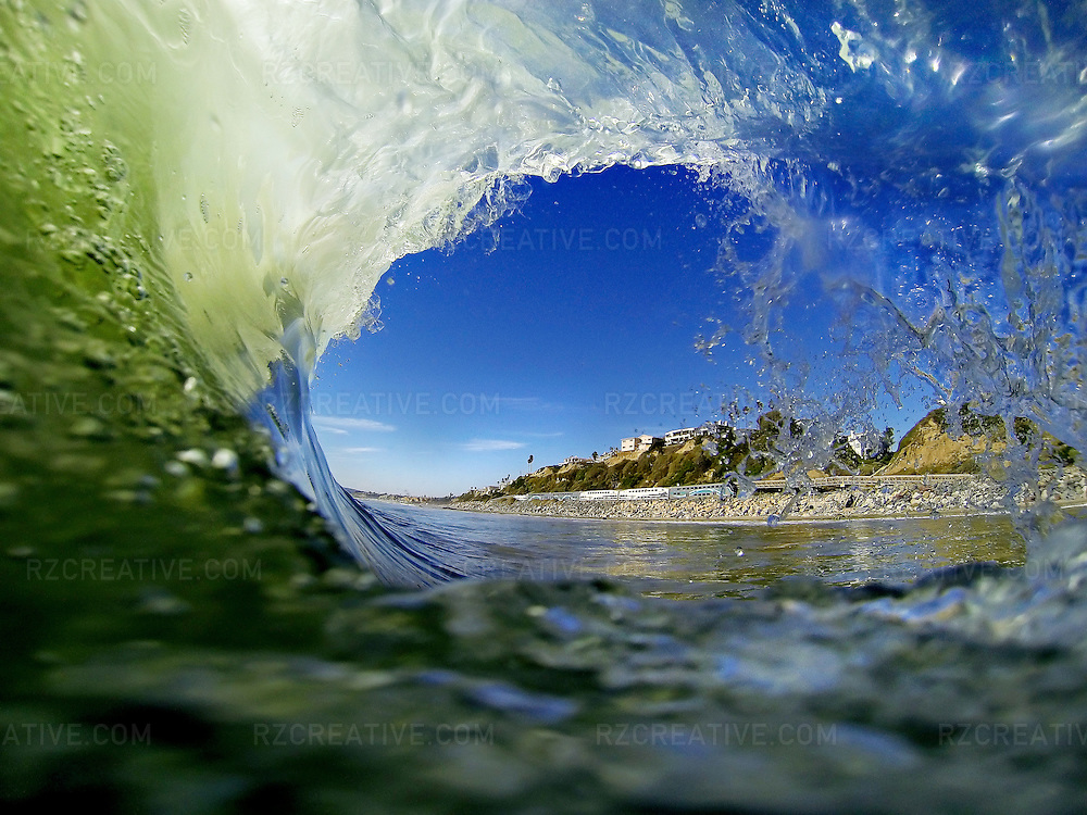 Unique perspective of the inside of a breaking wave near the pier in San Clemente. The coast can be seen passing by. Photo by Robert Zaleski/rzcreative.com