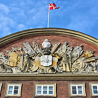 Ornate Frieze on The Red Building in Copenhagen, Denmark <br /> The bust above the crown and Denmark's coat of arms is Frederick IV who was the King of Denmark when this ornate frieze was carved on The Red Building in 1721. Also called the Building of Colleges, it is connected to the Christiansborg Palace on Slotsholmen island.  The Den Røde Bygning served as the Chancellery House until 1848.  It is now the offices of the Ministry of Finance.