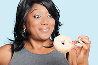 Overweight mixed race woman eating donut over blue background