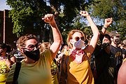 """28 JULY 2020 - DES MOINES, IOWA: Members of Des Moines' """"Wall of Moms"""" chant while they stand in front of the Governor's Mansion on Grand Ave in Des Moines. The Wall of Moms led the march to the mansion. About 150 supporters of Black Lives Matter marched from downtown to Des Moines to the Governor's Mansion. They were demanding that Iowa Governor Kim Reynolds restore the voting rights for felons who have completed their sentence. In June, Reynolds met with representatives of Black Lives Matter and promised to sign an executive order to restore voting rights, but she hasn't said anything more about it in six weeks. Iowa is now the only state in the US that permanently strips felons of their voting rights. That means 60,000 people in Iowa can't vote.    PHOTO BY JACK KURTZ"""