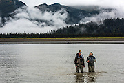 Dr. Joanne Edney walks through low tide with her brother out to the boat to take guests Halibut Fishing.
