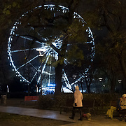 BUDAPEST, HUNGARY - DECEMBER 07:  An homeless woman sits on a bench in front of the Budapest Eye on December 7, 2017 in Budapest, Hungary. The traditional Christmas market and lights will stay until 31st December 2017.