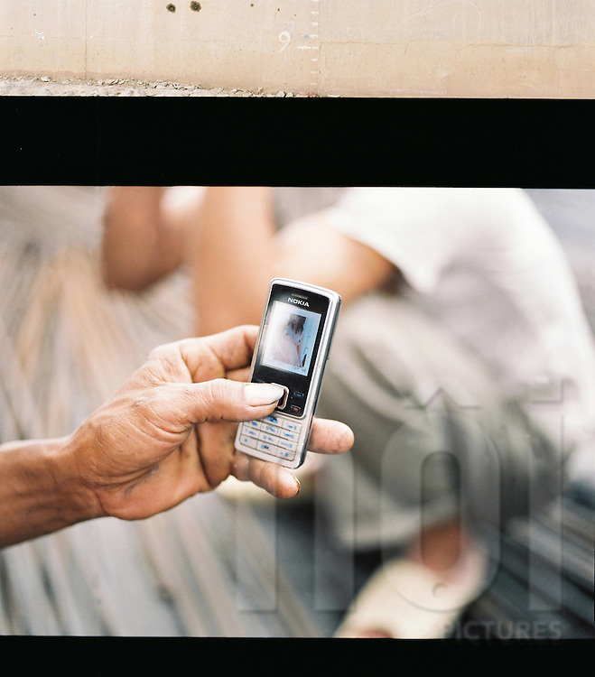 A worker shows a picture of a naked girl on the screen of his mobile phone. Hanoi, Vietnam, Asia