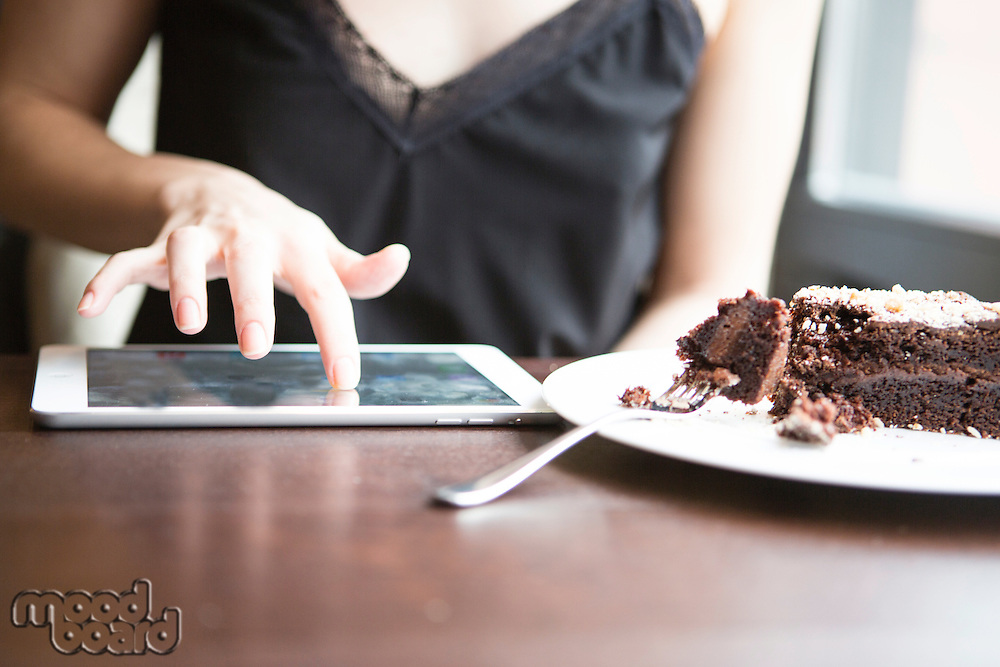 Midsection of woman using tablet PC by pastry in cafe