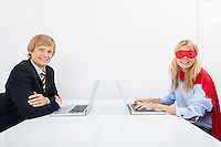 Portrait of smiling businessman with coworker in superhero costume using laptops at office