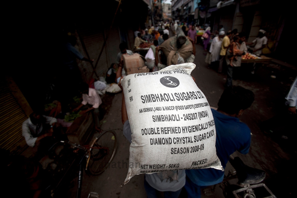 A man carries a 50 kg bag of sugar on his head, through the busy wholesale market of Old Delhi, in New Delhi, India, on Wednesday September 2, 2010. Photographer: Prashanth Vishwanathan/Bloomberg News