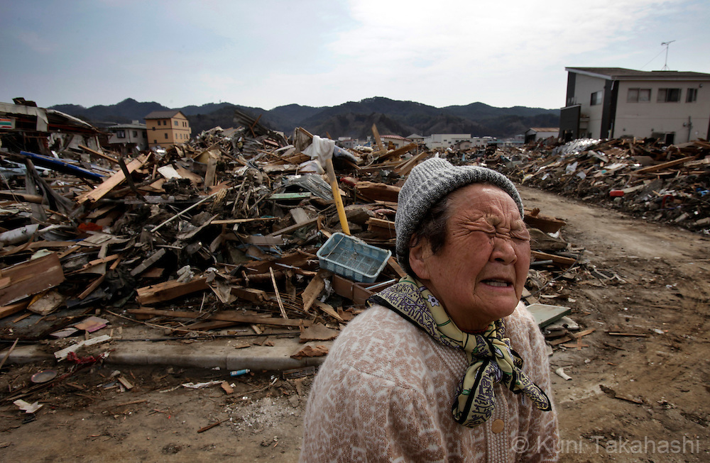 A woman, whose house was washed away, emotionally talks as debris scatter around Shinhamacyo area in Kesennuma, Miyagi, Japan on March 29, 2011after massive earthquake and tsunami hit northern Japan. More than 20,000 were killed by the disaster on March 11.<br /> Photo by Kuni Takahashi
