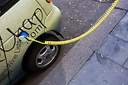 A power cable plugs into the place of a petrol cap while recharging an electronic Daimler-Chrysler-made Smart car.