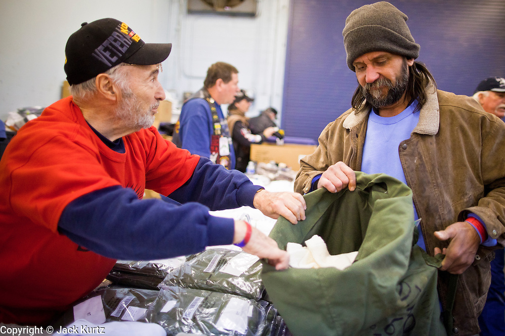 04 FEBRUARY 2011 - PHOENIX, AZ: BERNARD KAPLAN (left) a US Army veteran of the Korean and Vietnam Wars, helps DANIEL FURRER, a homeless Army vet, pick out some clean clothes at the Arizona StandDown Friday. The Arizona StandDown is an annual three day event that brings together the Valley's homeless and at-risk military veterans, connecting them with services ranging from: VA HealthCare, mental health services, clothing, meals, emergency shelter, transitional and permanent housing, ID/ drivers license's, court services and Legal Aide, showers, haircuts and myriad other services and resources. Arizona StandDown is held annually at the Veterans Memorial Coliseum at the Arizona State Fairgrounds in Phoenix on Super Bowl weekend.    Photo by Jack Kurtz